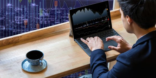 Businessman sitting and using computer laptop showing trading graph beside the windows glass over the Trading graph on the cityscape background, Business financial concept